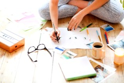 Young brunette woman creating her Feng Shui wish map using scissors. Dreams and wishes