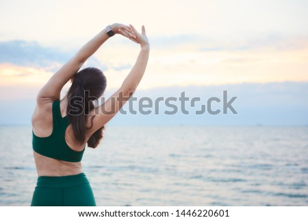 Young brunette woman exercising at the sea shore at sunrise listening to the music. #1446220601