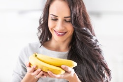 Young brunette woman holding a bunch of bananas.