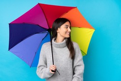 Young brunette woman holding an umbrella over isolated blue wall looking to the side