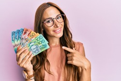 Young brunette woman holding australian dollars smiling happy pointing with hand and finger