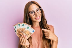Young brunette woman holding bunch of 50 euro banknotes smiling happy pointing with hand and finger