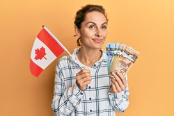 Young brunette woman holding canada flag and dollars smiling looking to the side and staring away thinking.