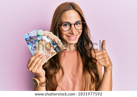 Young brunette woman holding canadian dollars smiling happy and positive, thumb up doing excellent and approval sign  Photo stock ©
