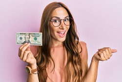 Young brunette woman holding 20 dollars banknote pointing thumb up to the side smiling happy with open mouth