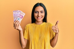 Young brunette woman holding 50 mexican pesos banknotes smiling happy and positive, thumb up doing excellent and approval sign