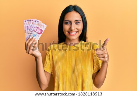Young brunette woman holding 50 mexican pesos banknotes smiling happy and positive, thumb up doing excellent and approval sign  Foto stock ©