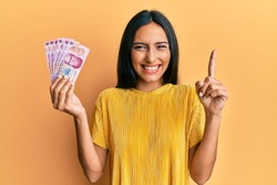 Young brunette woman holding 50 mexican pesos banknotes smiling with an idea or question pointing finger with happy face, number one