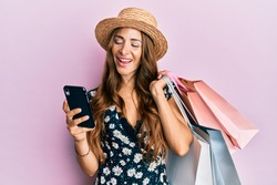Young brunette woman holding shopping bags and smartphone smiling and laughing hard out loud because funny crazy joke.