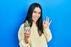 Young brunette woman holding small cactus pot doing ok sign with fingers, smiling friendly gesturing excellent symbol