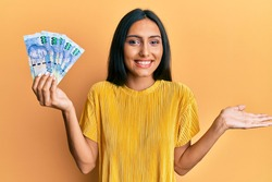 Young brunette woman holding south african 100 rand banknotes celebrating achievement with happy smile and winner expression with raised hand