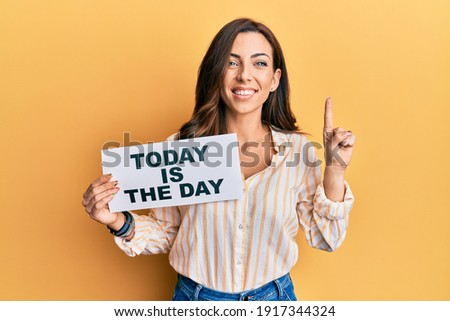 Young brunette woman holding today is the day smiling with an idea or question pointing finger with happy face, number one  Stock photo ©