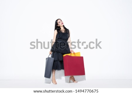 Young brunette woman in black dress shopping on white background. Attractive caucasian female model. Finance, black friday, cyber monday, sales, autumn concept. Copyspace. Dreamful, attented. #1494770675