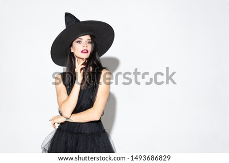 Young brunette woman in black hat and costume on white background. Attractive caucasian female model. Halloween, black friday, cyber monday, sales, autumn concept. Copyspace. Looks confident.