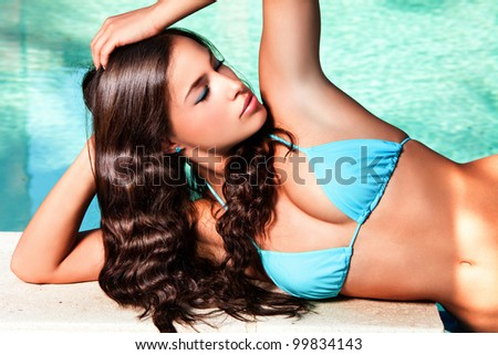 young brunette woman in blue bikini resting by the pool