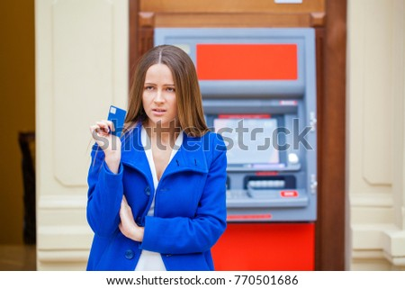 0d983fc03b9c Young brunette woman in blue coat withdrawing money from credit card at ATM  #770501686