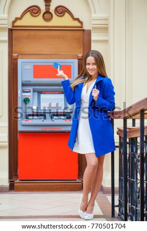 80b966fc3f8c Young brunette woman in blue coat withdrawing money from credit card at ATM  #770501704