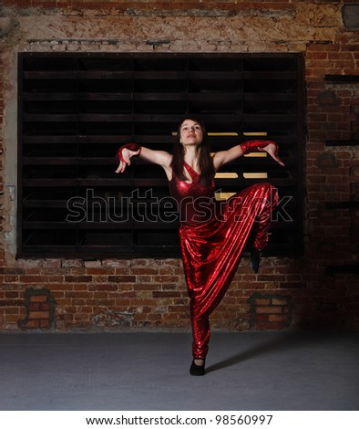Young brunette woman in red dancing over brick wall