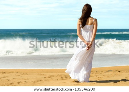 Young brunette woman in summer white dress standing on beach and looking to the sea. Caucasian girl relaxing and enjoying peace on vacation.