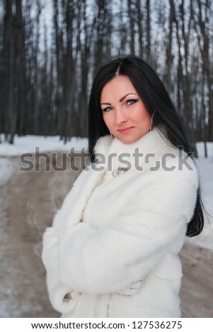 Young brunette woman in white fur coat in winter forest