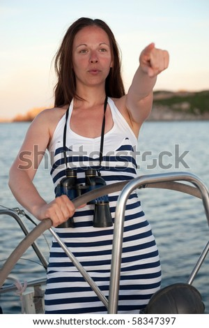 young brunette woman on the yacht points to the horizon