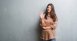 Young brunette woman over grunge grey wall showing and pointing up with fingers number five while smiling confident and happy.
