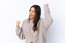 Young brunette woman over isolated white background celebrating a victory