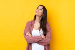 Young brunette woman over isolated yellow background looking up while smiling