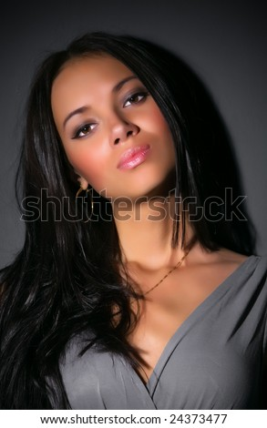 Young brunette woman portrait. On dark wall background.