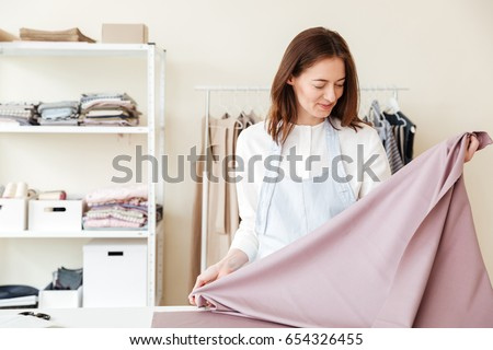 Young brunette woman seamstress looking at pink fabrics and standing in workshop