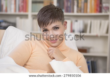 Young brunette woman sitting in front of bookshelf