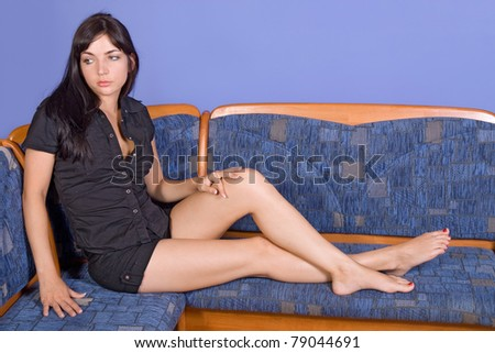 Young brunette woman sitting on bench - stock photo