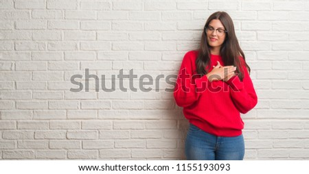 Young brunette woman standing over white brick wall smiling with hands on chest with closed eyes and grateful gesture on face. Health concept.