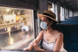Young brunette woman traveling in Thailand on train during pandemic Coronavirus. 20s Hispanic in a protective mask wear summer sleeveless clothes and backpack in Asia.