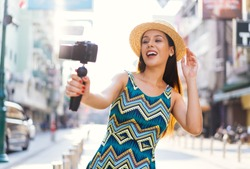 Young brunette woman using a video camera to record journey with smile. Happy and excited 20s Hispanic girl traveler wear summer dress with hat waving to internet audience. Influencer vlogging concept