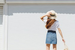 Young brunette woman wearing blue denim mini skirt, white t-shirt and boater hat walking near white roller door. Trendy casual summer or spring outfit. Street fashion. Back view. In motion.