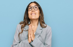 Young brunette woman wearing business clothes begging and praying with hands together with hope expression on face very emotional and worried. begging.