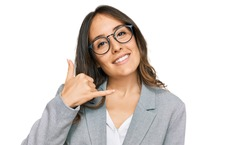Young brunette woman wearing business clothes smiling doing phone gesture with hand and fingers like talking on the telephone. communicating concepts.