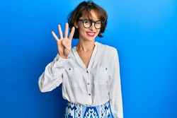 Young brunette woman wearing casual clothes and glasses showing and pointing up with fingers number four while smiling confident and happy.