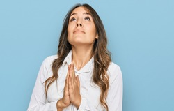 Young brunette woman wearing casual clothes begging and praying with hands together with hope expression on face very emotional and worried. begging.