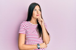 Young brunette woman wearing casual clothes over pink background with hand on chin thinking about question, pensive expression. smiling and thoughtful face. doubt concept.