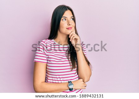 Young brunette woman wearing casual clothes over pink background with hand on chin thinking about question, pensive expression. smiling and thoughtful face. doubt concept.  Photo stock ©