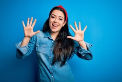 Young brunette woman wearing casual denim shirt over blue isolated background showing and pointing up with fingers number ten while smiling confident and happy.