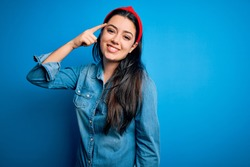Young brunette woman wearing casual denim shirt over blue isolated background Smiling pointing to head with one finger, great idea or thought, good memory