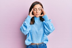 Young brunette woman wearing casual winter sweater over pink background with hand on head for pain in head because stress. suffering migraine.