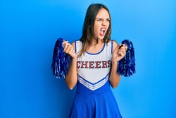 Young brunette woman wearing cheerleader uniform angry and mad screaming frustrated and furious, shouting with anger. rage and aggressive concept.