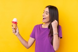 Young brunette woman with a cornet ice cream over isolated yellow background celebrating a victory