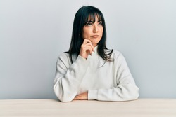 Young brunette woman with bangs wearing casual clothes sitting on the table thinking concentrated about doubt with finger on chin and looking up wondering