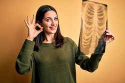 Young brunette woman with blue eyes holding xray of lungs over yellow background doing ok sign with fingers, excellent symbol