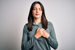 Young brunette woman with blue eyes wearing casual green sweater over white background smiling with hands on chest with closed eyes and grateful gesture on face. Health concept.
